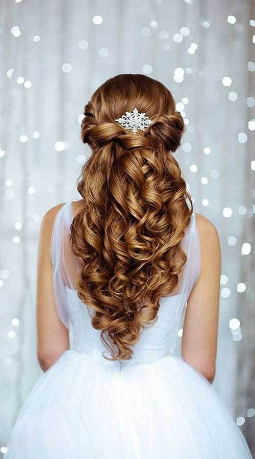 an elegant twisted and curly half updo accessorized with a shiny snowflake hairpiece