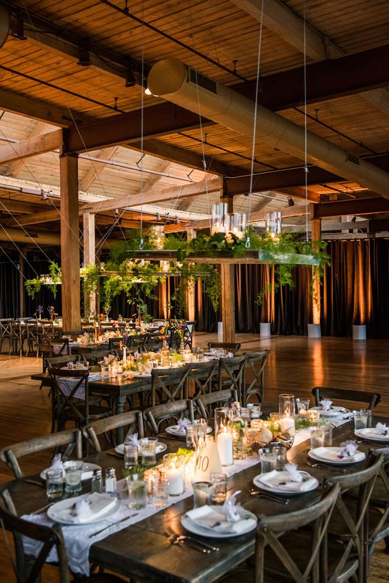 hangings with lush greenery and candles and candles on the tables to create an ambience