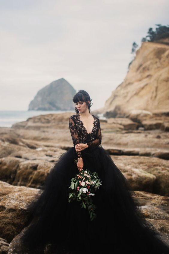 a unique black wedding gown with a lace bodice and sleeves, a deep V-neckline and a fulle layered skirt