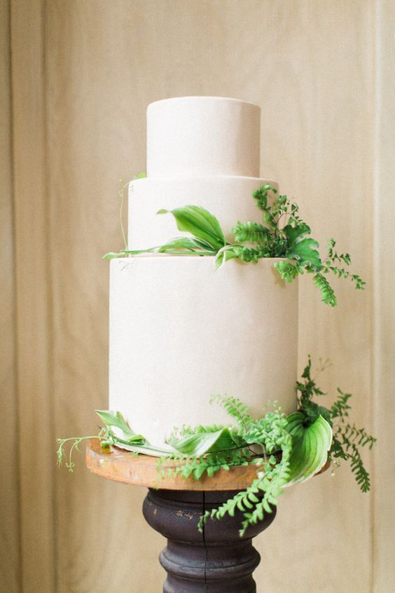 a white frosted wedding cake with lush greenery is all you need for a modern touch