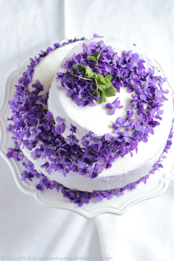 a white wedding cake with violet blooms on top and some greenery is ideal for a summer wedding