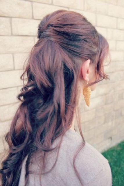 twisted half updo with waves and bangs and volume on top looks trendy and fashionable
