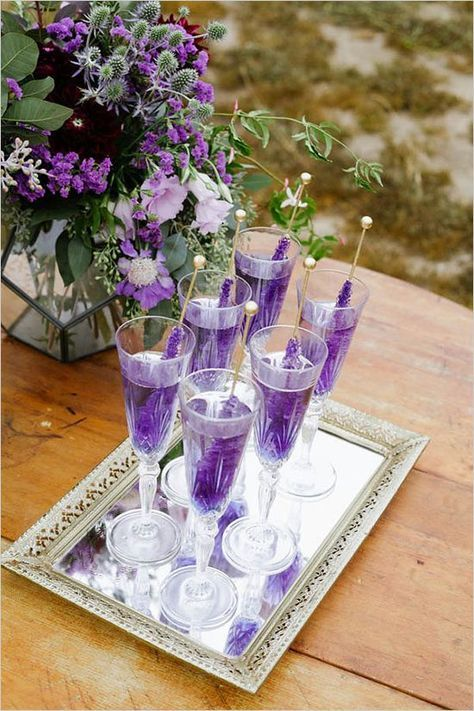 violet wedding cocktails with sugar rock candies on a vintage mirrored tray