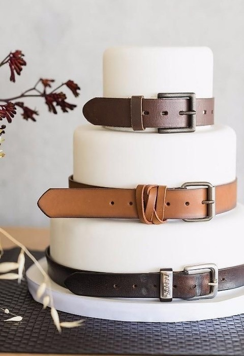 white fondant wedding cake with brown leather belts for an industrial wedding