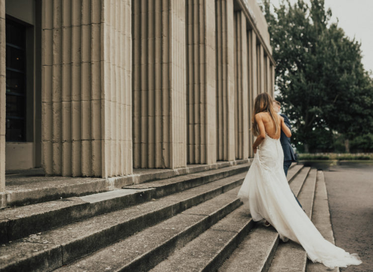 The bride was wearing a backless spaghetti strap wedding dress with a train