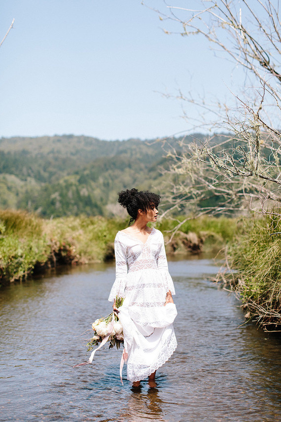 The bride was wearing a boho lace wedding dress with bell sleeves and a natural curly hairstyle