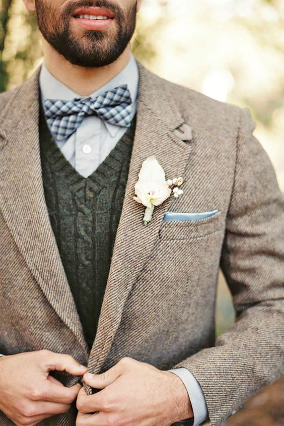 a light blue shirt, a cable knit waistcoat, a checked bow tie and a brown tweed jacket