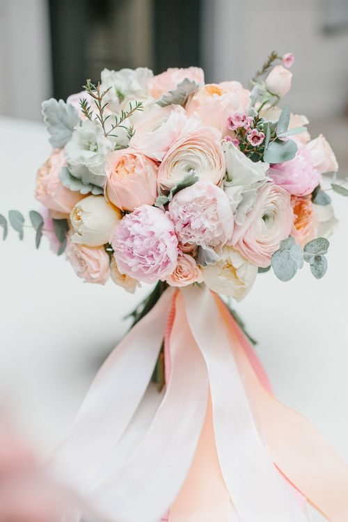 coral and pink wedding bouquet with pale eucalyptus and ribbons looks very chic