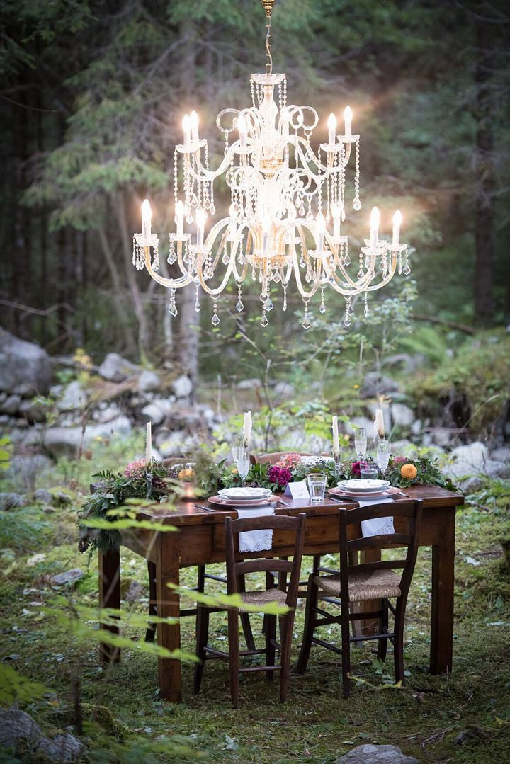 An oversized glam chandelier over the tablescape with a lush table runner were styled exactly for the shoot