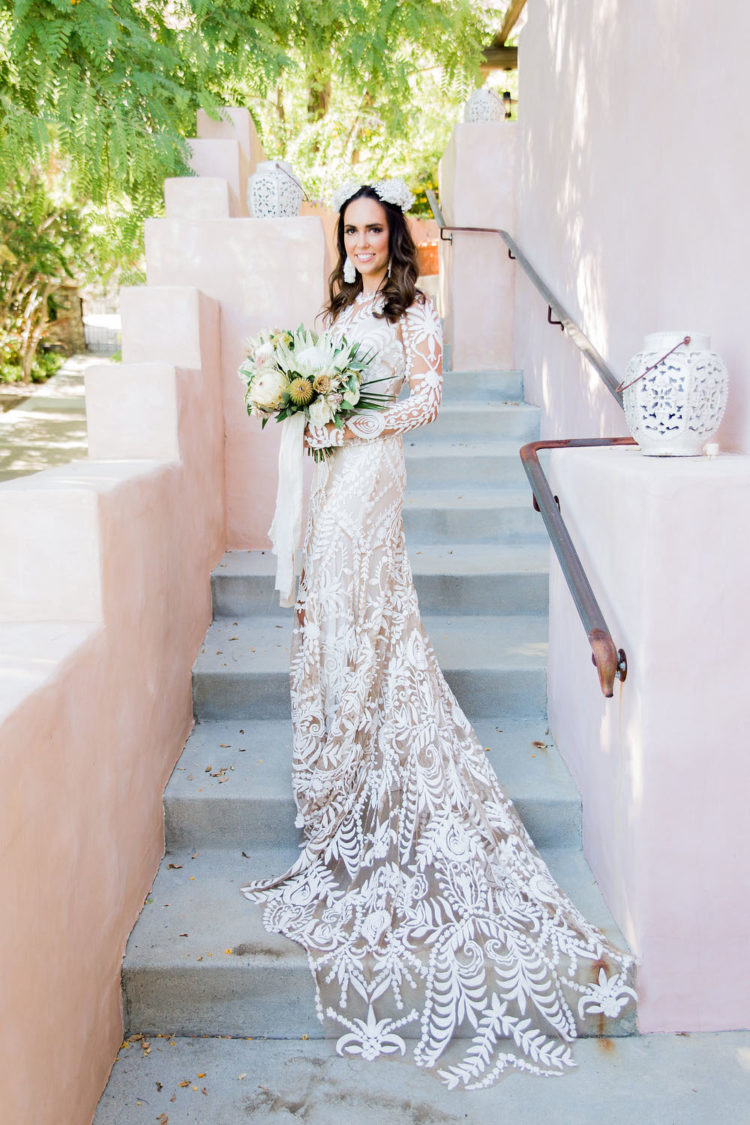 The bride was wearing a boho wedding gown with large lace appliques and illusion parts and completed the look with statement earrings and a crown