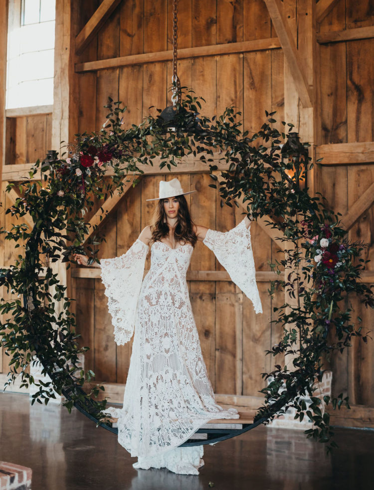 The bride was wearing a strapless boho lace wedding dress with removable sleeves and a matching hat