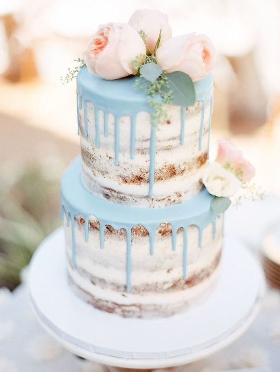 a naked wedding cake with powder blue drip and blush peonies looks very spring-like
