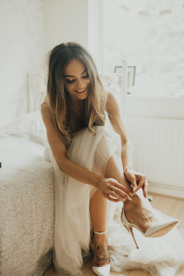 She was rocking strap embellished wedding heels, a casual hairstyle and a nude lip