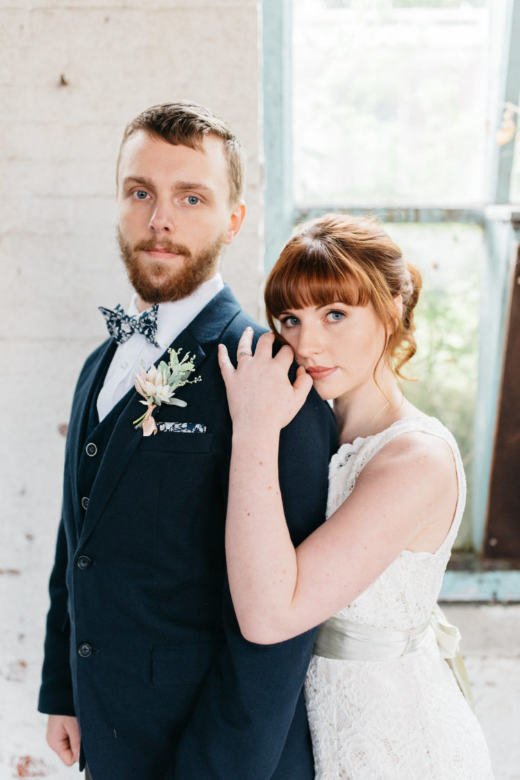 The groom was wearing a navy three-piece suit with a printed bow tie and a cute boutonniere