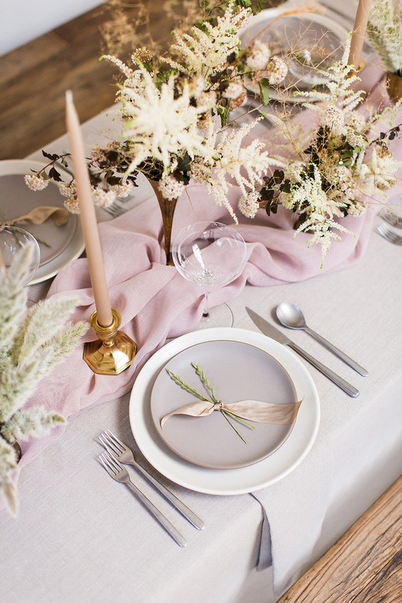 The wedding tablescape was done with a white tablecloth, a pink table runner, blush candles and cremay and grey plates