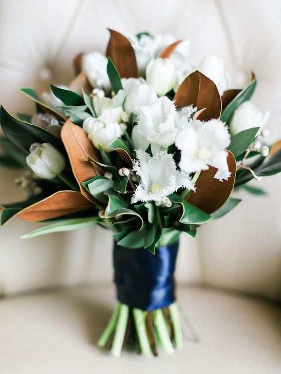 a chic and fresh wedding bouquet with white tulips and magnolia leaves