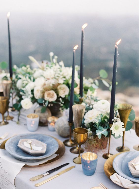 a moody spring table setting with slate blue candles, brass glasses and goblets, stone-inspired plates and marbeleized candle holders