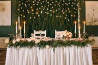 04 lush greenery with white blooms and candles on top for a woodland-inspired wedding