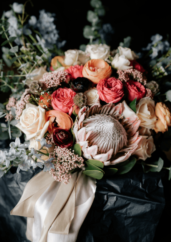 The bridal bouquet featured roses, a king protea, eucalyptus and other blooms, it was lush and bold
