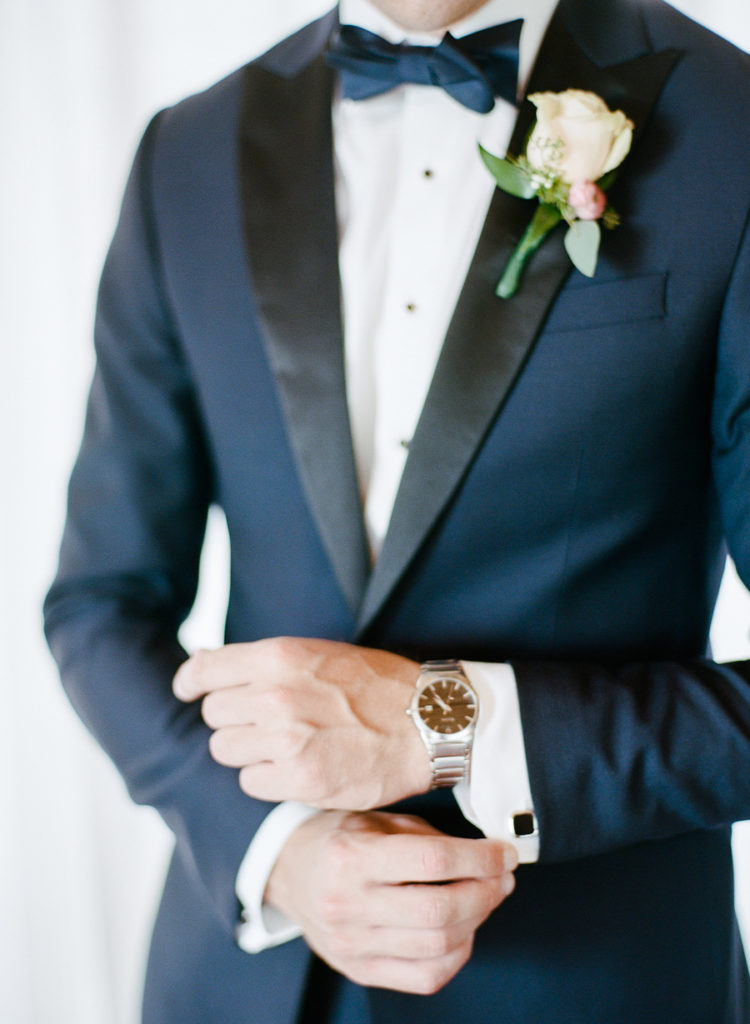 The groom was wearing a navy tuxedo with black lapels and a bow tie