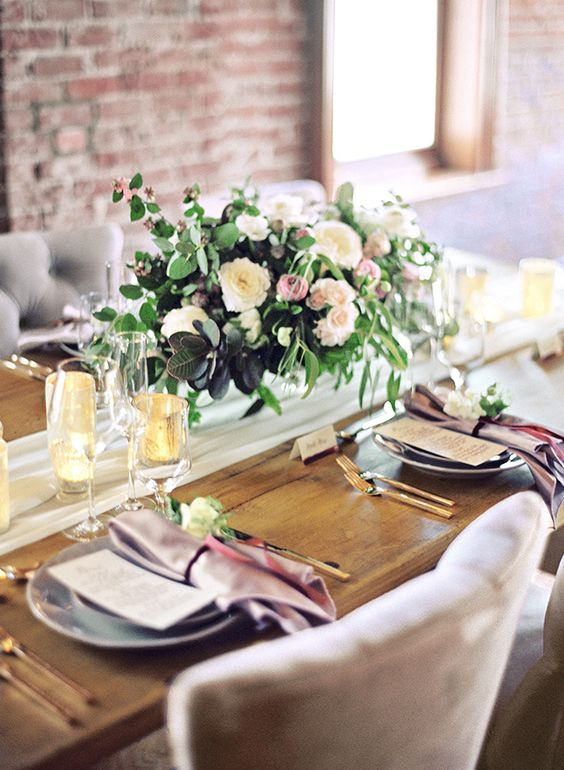 a cool tablescape with purple napkins, gilded touches and a moody floral centerpiece of blush and white blooms and greenery