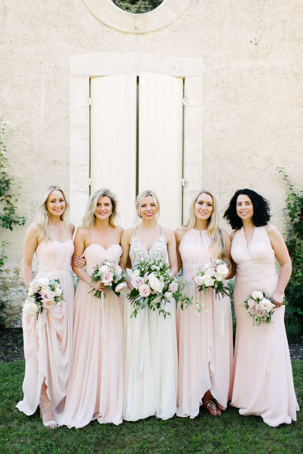 The bridesmaids were wearing mismatching blush gowns and holding romantic blooms