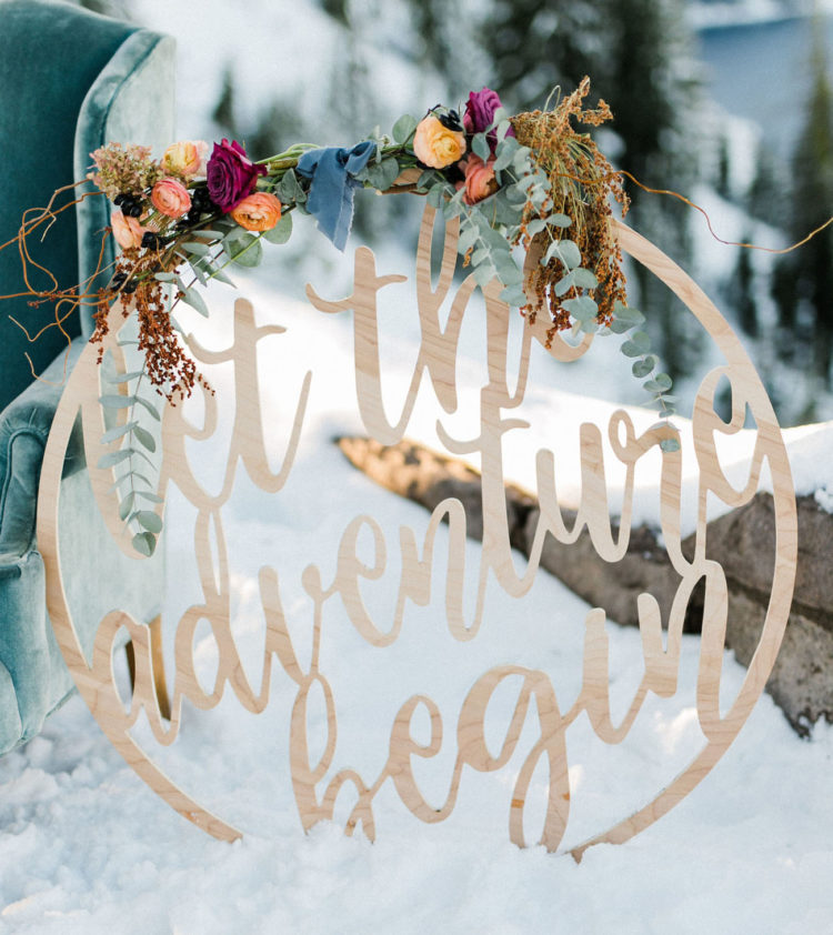 A creative wedding sign decorated with colorful blooms and greenery