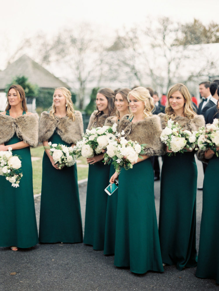 The bridesmaids were wearing mismatched emerald gowns and covered up with faux fur stoles