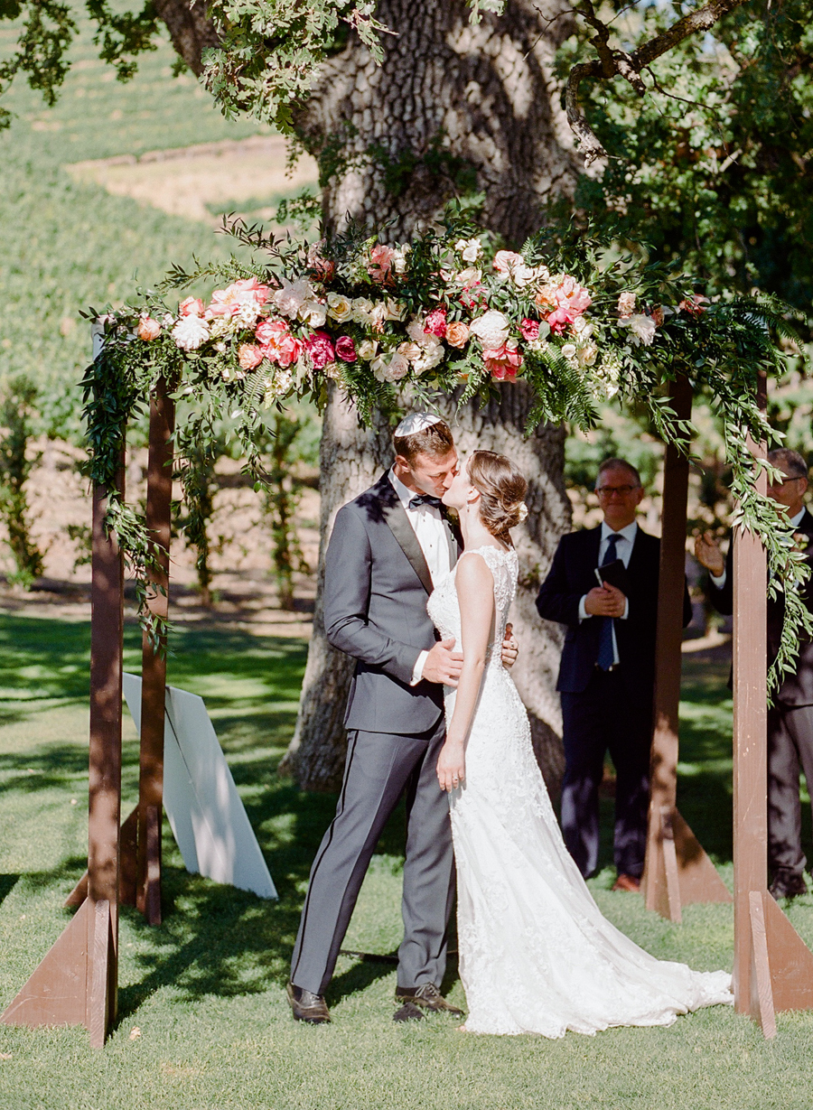 There was a lush decorated wedding chuppah with greenery and florals