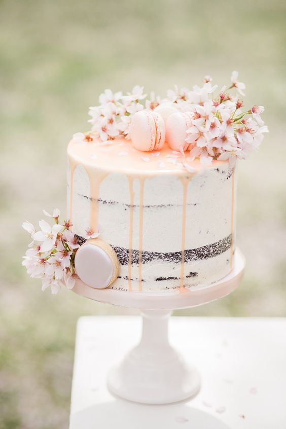 a semi naked wedding cake with blush drip, cherry blossom and blush macarons