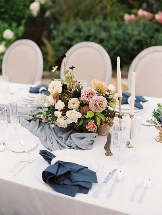 a spring tablescape with navy napkins and moody florals plus touches of grey
