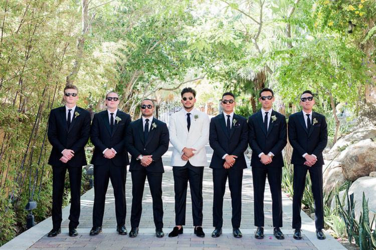 The groomsmen were wearing black tuxedos to make the groom stand out