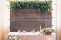 08 a barnwood backdrop with lush greneery on top and lights on its sides