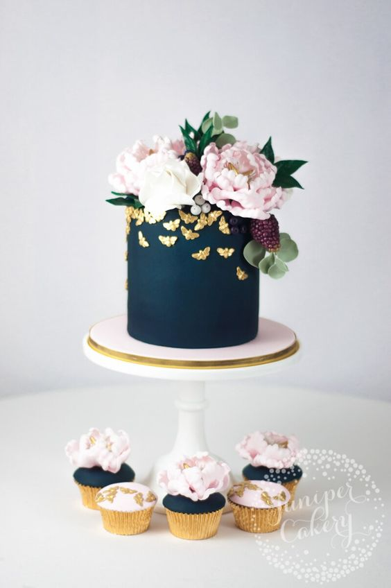 a matte navy wedding cake topped with lush blooms and greenery