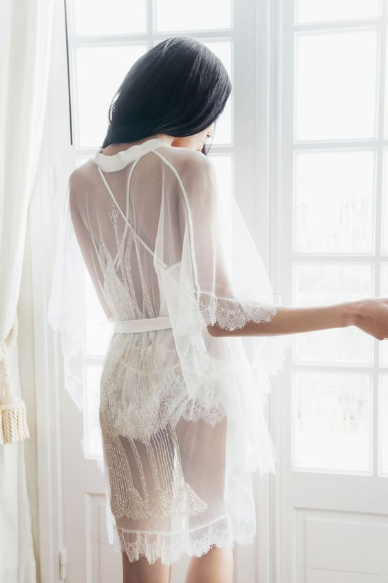a short sheer bridal robe with half sleeves, a lace trim and gold embroidery over a white lace romper for the wedding day