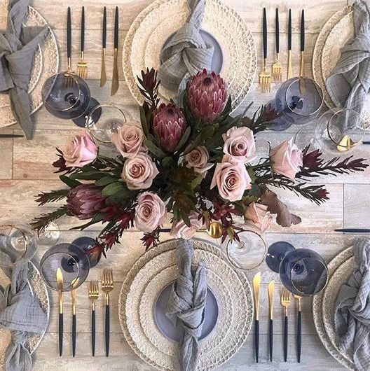 an elegant tablescape in greys and with gold touches plus a lush floral centerpiece with blush roses and proteas