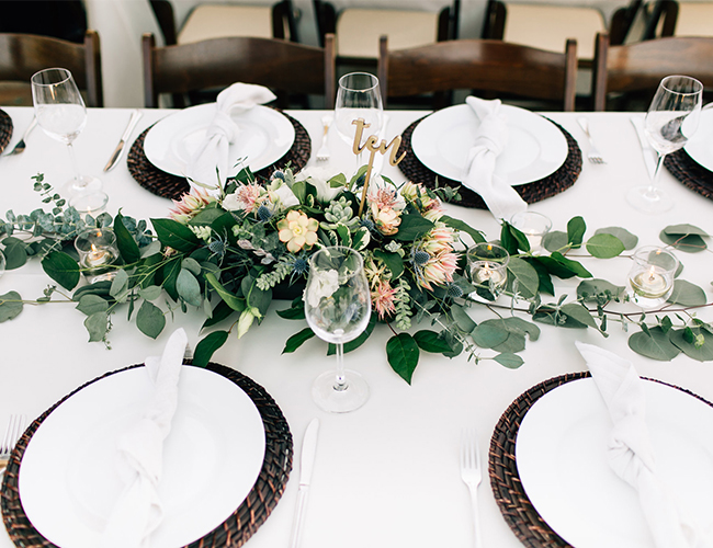 The tables were decorated in a chic and refreshing way, with lush florals and wicker chargers