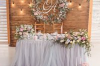 09 a barnwood backdrop with lush greenery and a floral wreath plus monograms