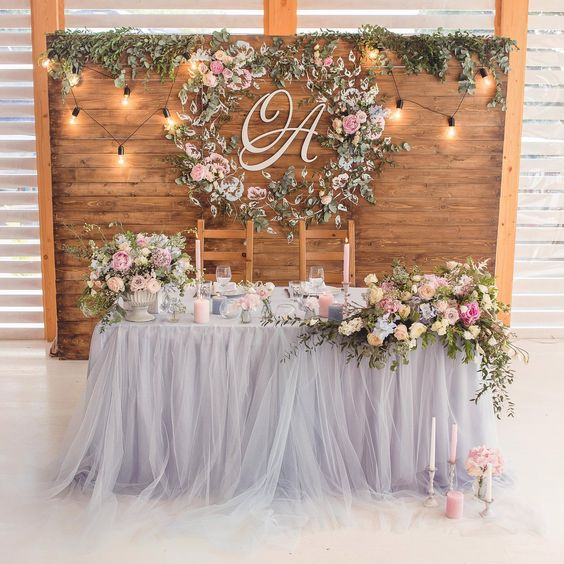 a barnwood backdrop with lush greenery and a floral wreath plus monograms