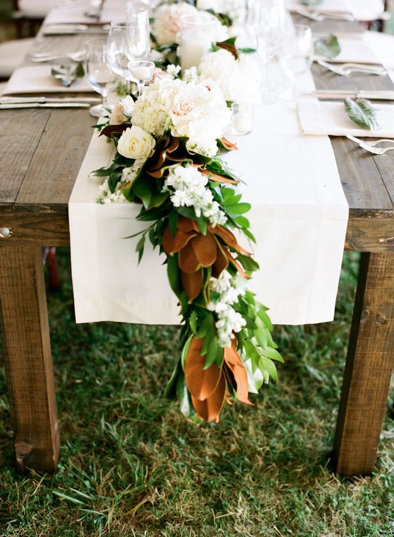 a magnolia leaf garland can be accessorized with neutral blooms for a chic look