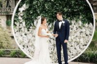 09 a minimalist wedding backdrop with greenery and white blooms is a chic statement