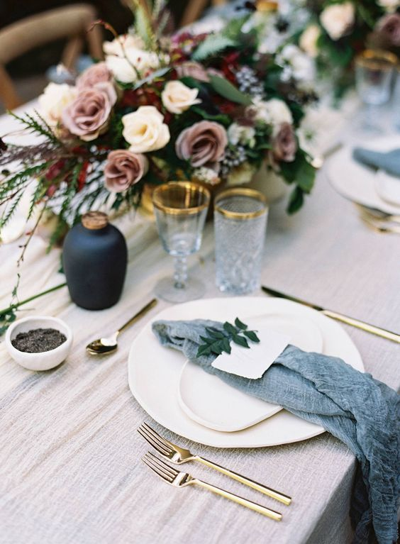 an ethereal and moody tablescape with slate grey napkins, gold rim glasses and moody florals looks chic