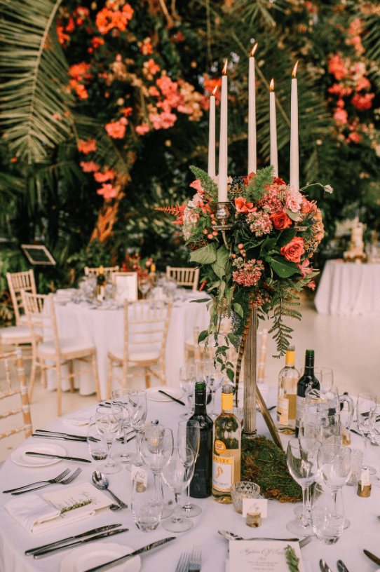 The tables were decorated with moss, candles and lush florals and greenery