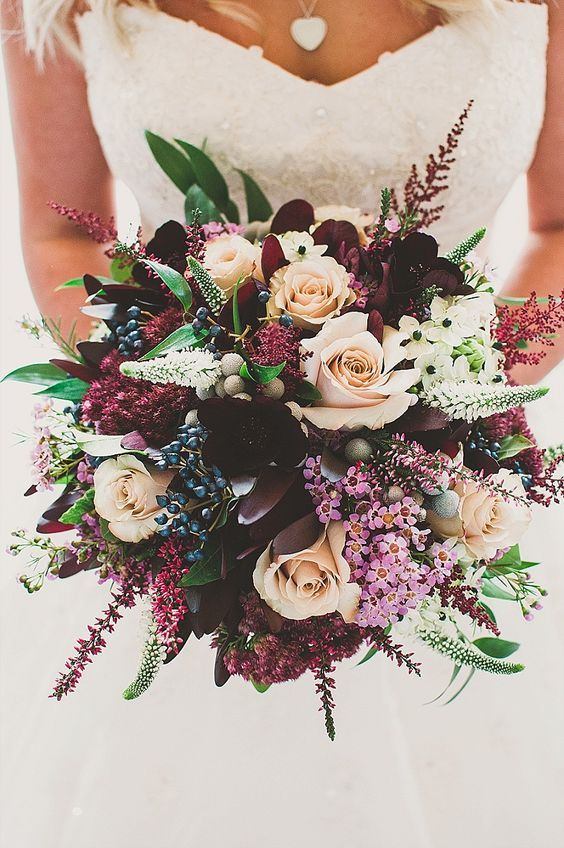 a bold and lush bridal bouquet with deep purple, burgundy and fuchsia blooms