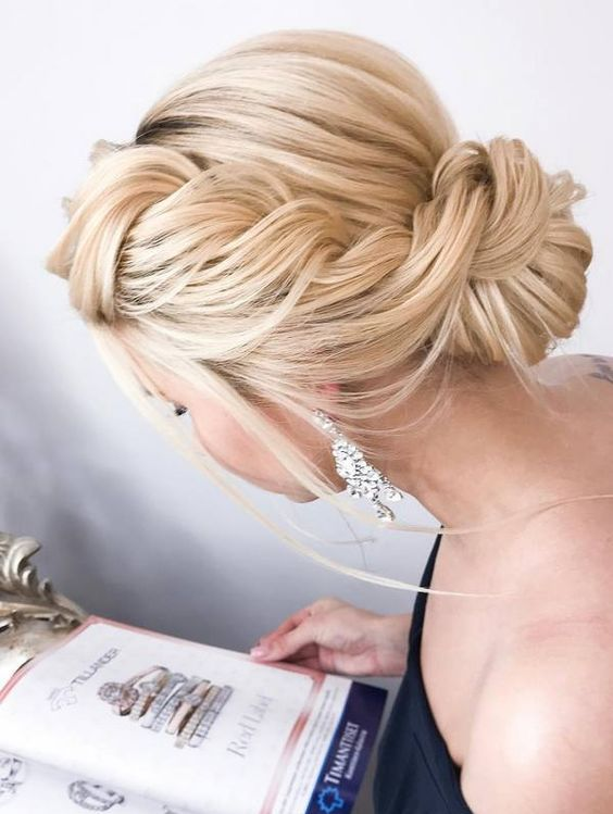a large sided braided updo with a low bun and some locks down is super chic and refined