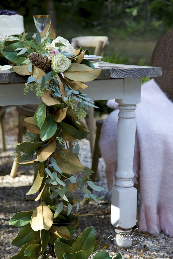a lush table runner with magnolia leaves, eucalyptus, pinecones and some blooms