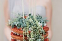 10 a naked wedding cake with strawberries, fresh greenery and candles on top