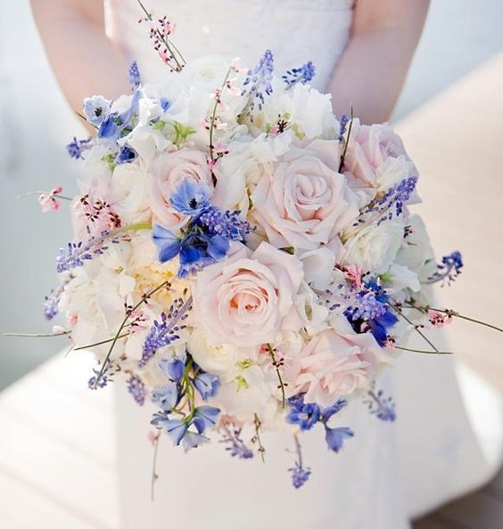 a pastel bouquet with bold touches of blue Muscari, blue delphinium, pink genestra and blushing roses
