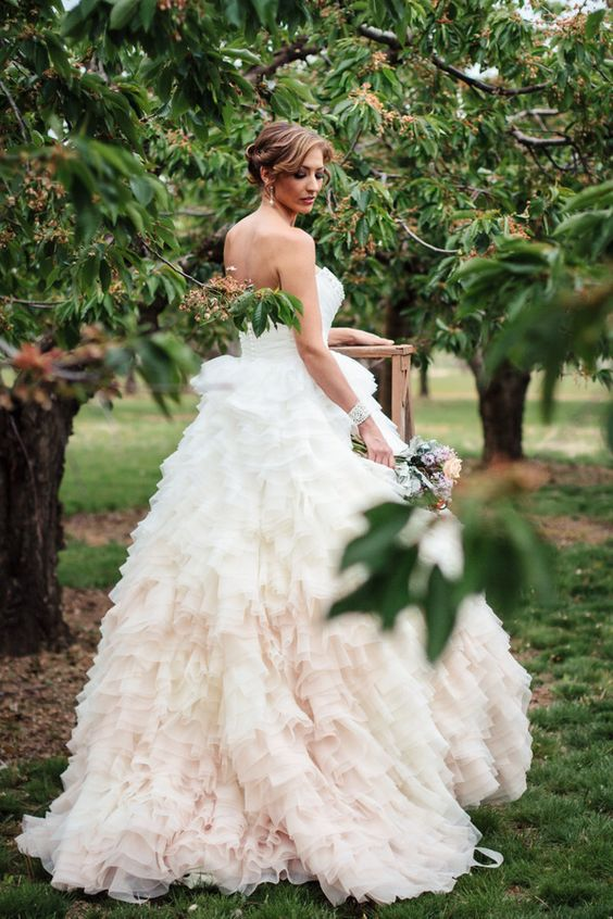a refined strapless wedding dress with a full ruffled blush ombre skirt