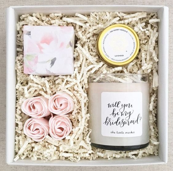 a simple box with a candle, balm, a wrapped soap and some faux blooms